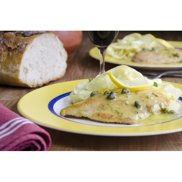 Chicken picatta served with wine and rustic bread.