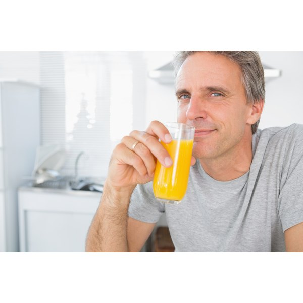 A man enjoys his orange juice in the morning.