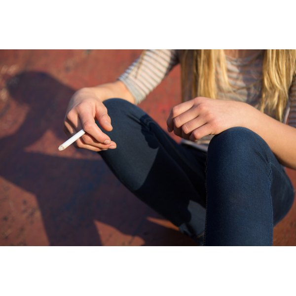A close-up of a teenage girl with a lit cigarette in her hand.