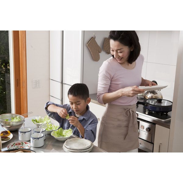 An Asian mother and son prepare a meal in their kitchen