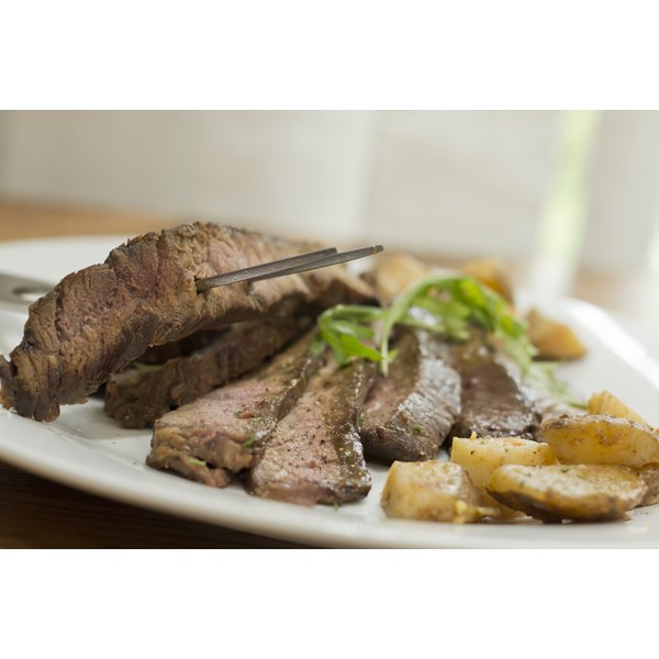 appealing image of cooked flank steak on plate with garnish in kitchen setting