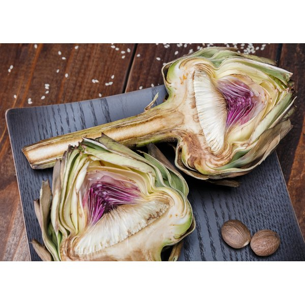 Two artichoke hearts on a cutting board.
