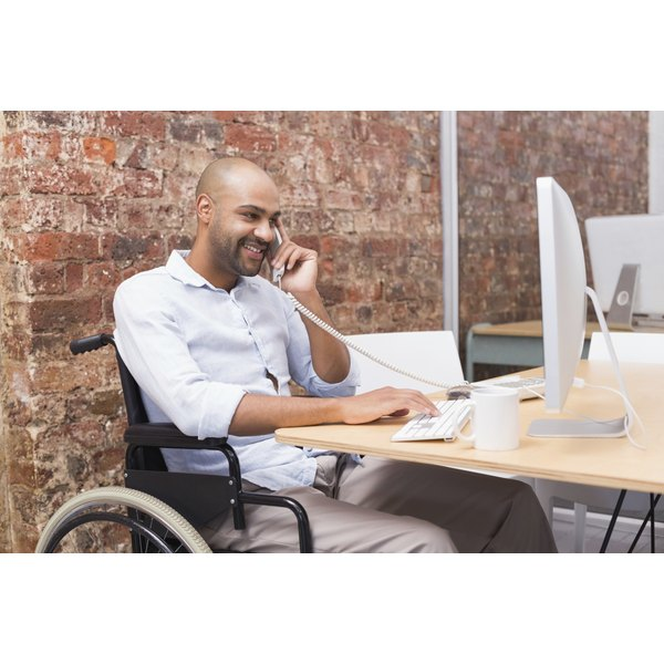 Man in wheelchair talking on the phone and working on a computer
