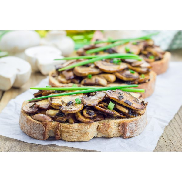 Sauteed mushrooms and fresh chives on slices of rustic bread.