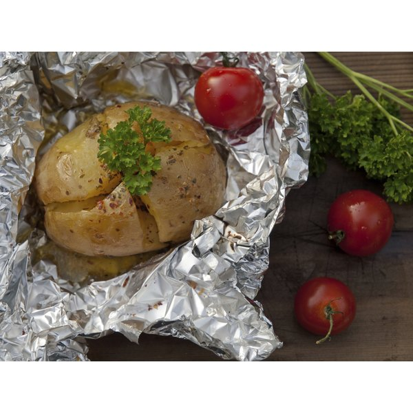 potato in foil with garnish on wood table