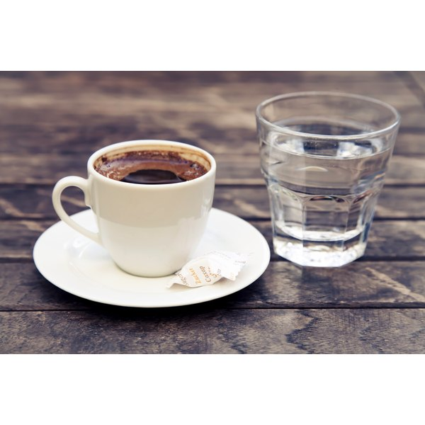 An espresso and glass of water on a table.