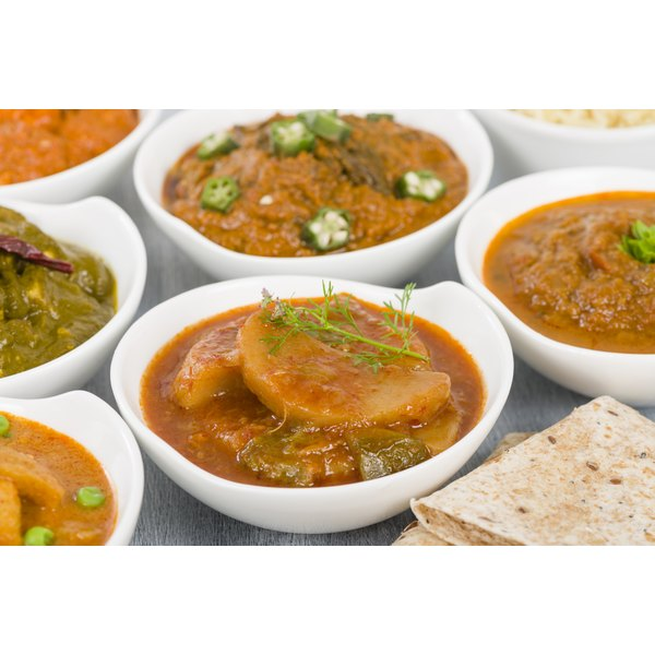 A range of vegetarian curries in white dishes sit on a table.