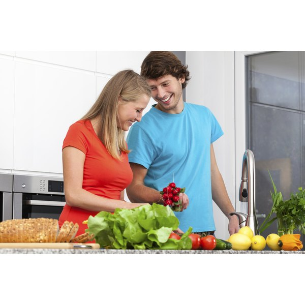 A young man and woman in the kitchen with fruits and vegetables.
