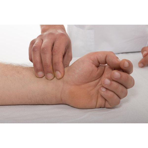 A doctor presses on a patient's arterial vein in the wrist.