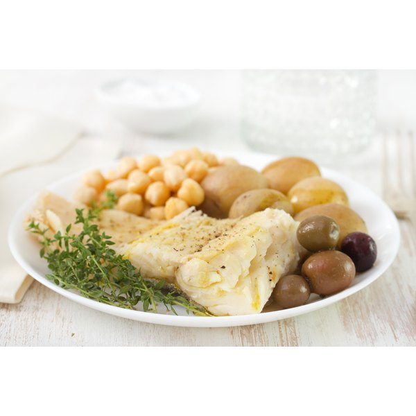 A plate with cooked cod fish and chickpeas.