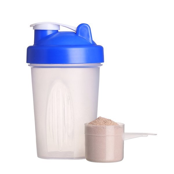 A shaker cup and a scoop of protein powder sit on a white counter.