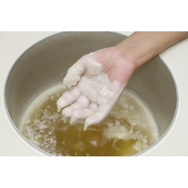 A Close Up Of Woman Putting Her Hand In Paraffin Wax Bath