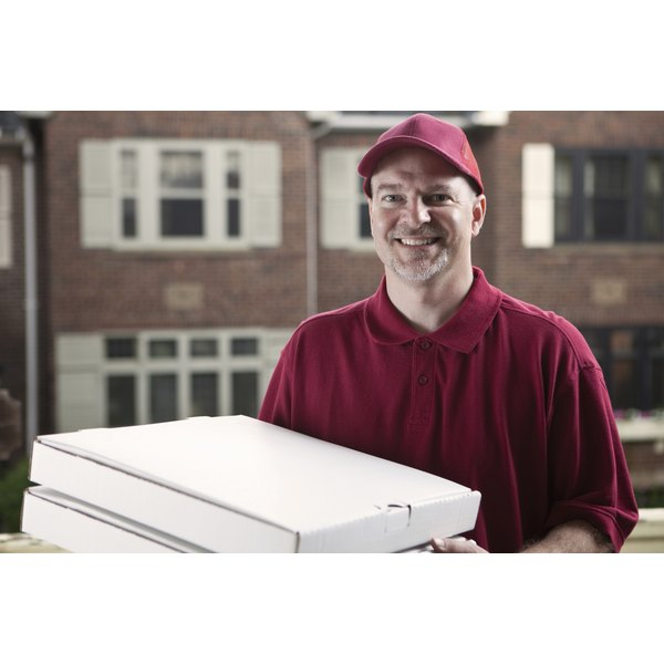 A pizza delivery man holding boxes of pizza.