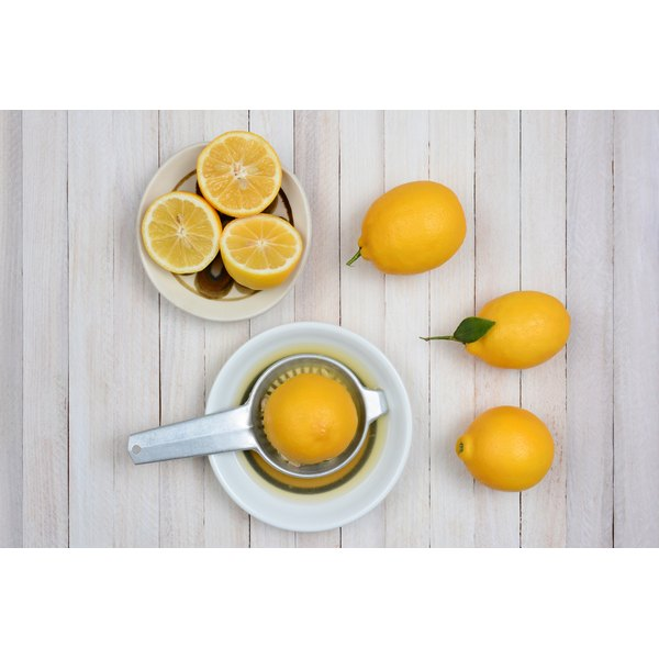Whole and halved lemons next to a juicer.