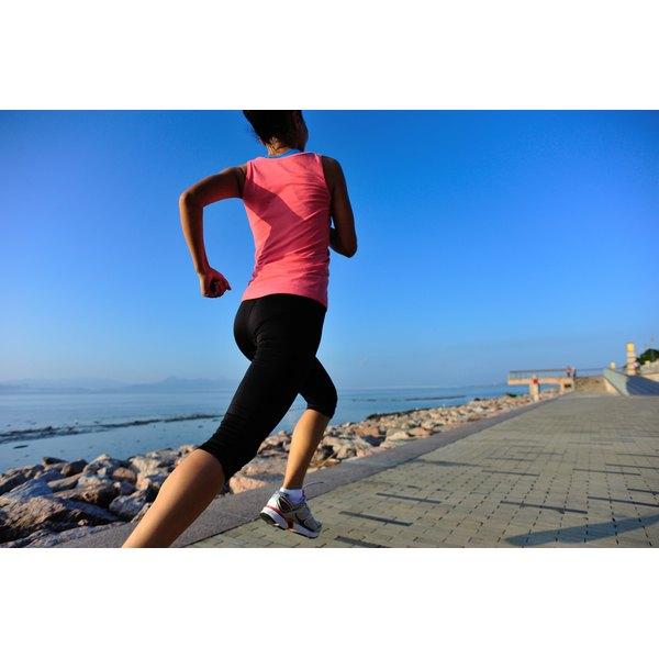 A woman runs along a coastal trail.