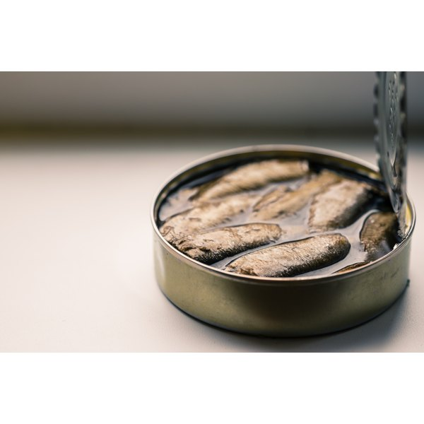 An opened can of sardines on a table.