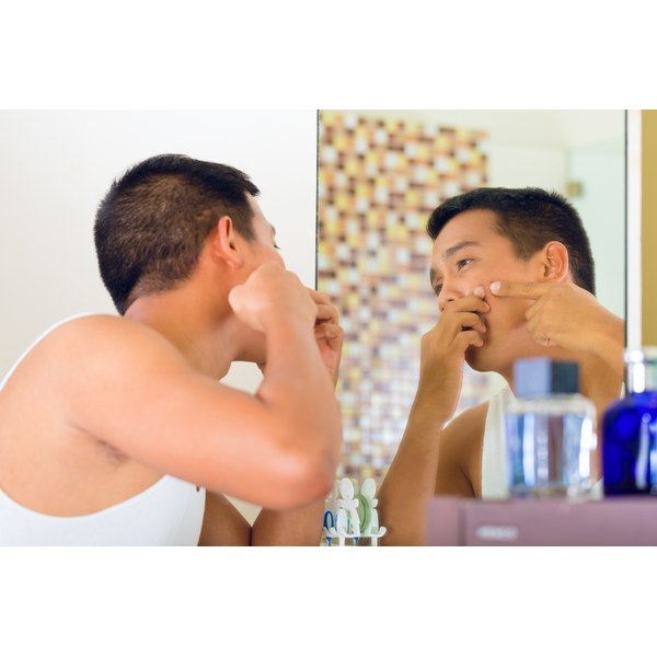 A man is popping a pimple in the mirror.