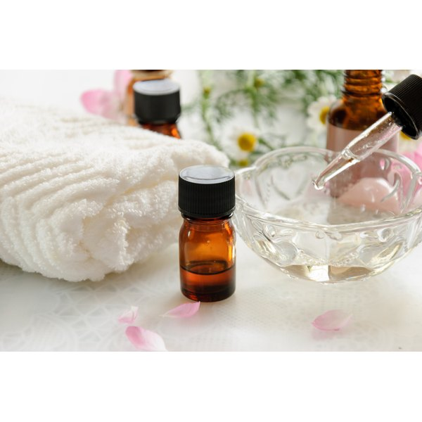 Bottles of essential oils and flower petals on a counter with a bowl and dropper.