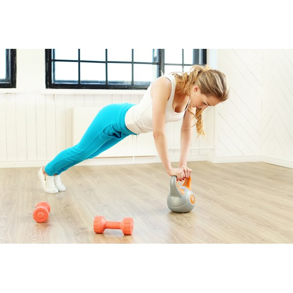 A woman is training using a kettlebell.