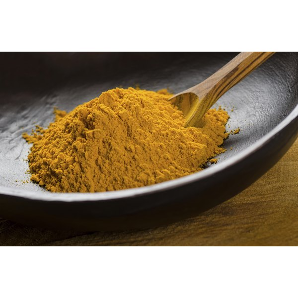 Ground tumeric in bowl with wooden spoon