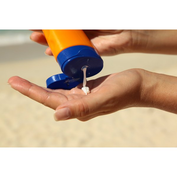 A woman's hands as she squeezes suntan lotion into the palm of her hand.