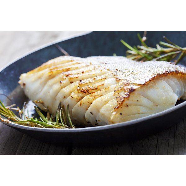 A seasoned pan-fried cod filet with fresh rosemary.