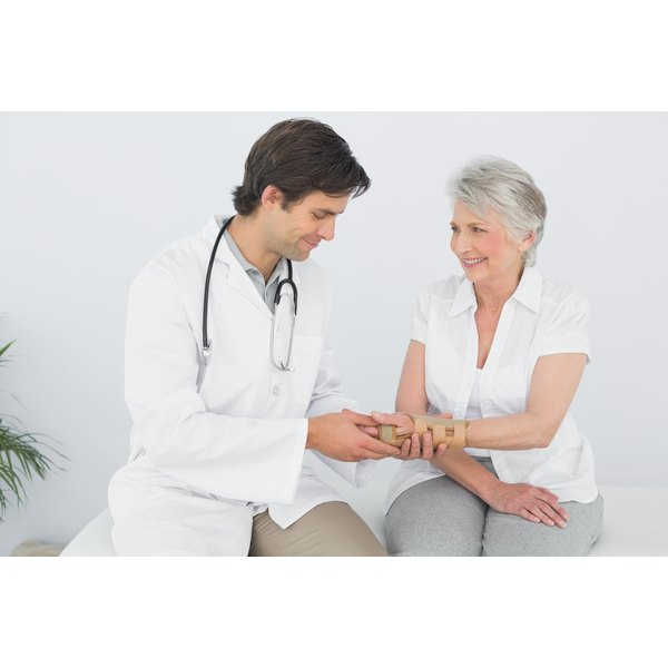 Doctor looking at elderly female patient's wrist.