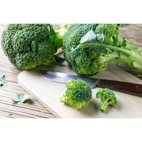 Florets of broccoli on a cutting board.