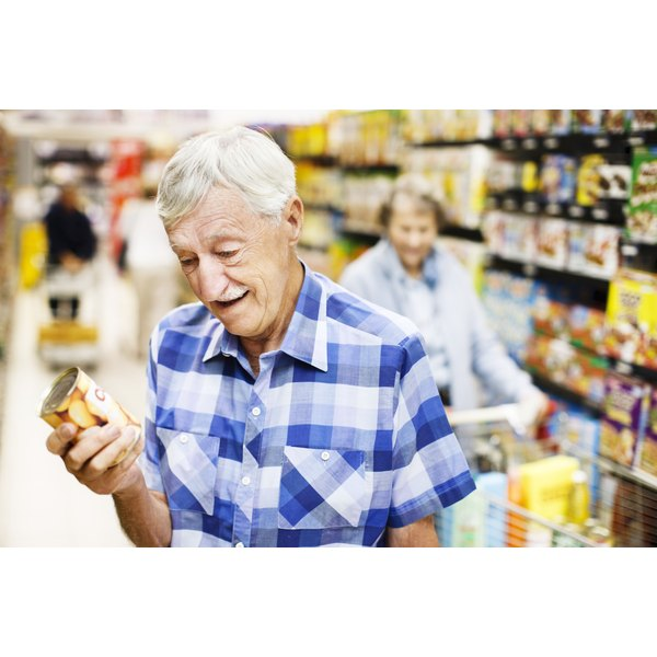 An older couple read the label on canned foods.