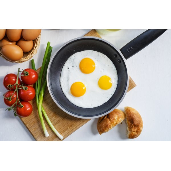 A large frying pan with three eggs in it.