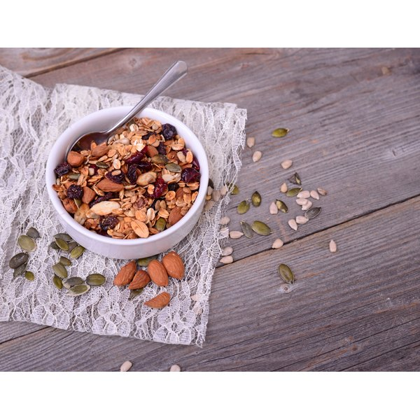 Granola containing freeze-dried fruits in it sits on a wooden table.