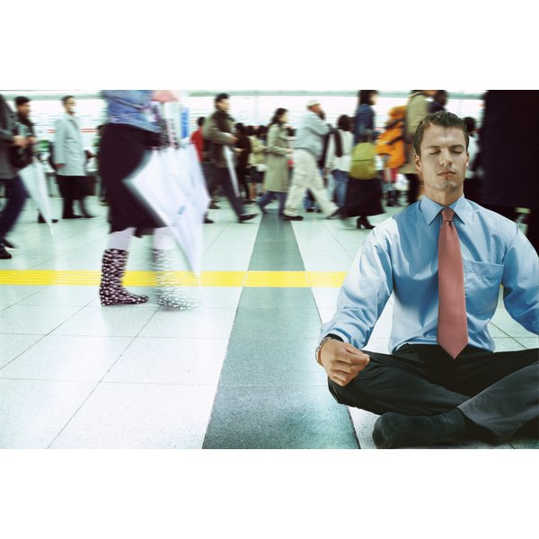 A young business man meditating in a busy public area.