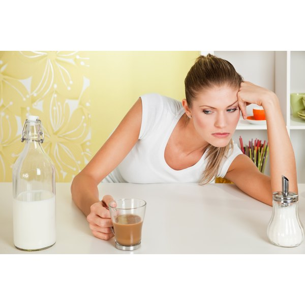A woman looking sorrowfully at a bottle of milk while holding a cup of coffee.