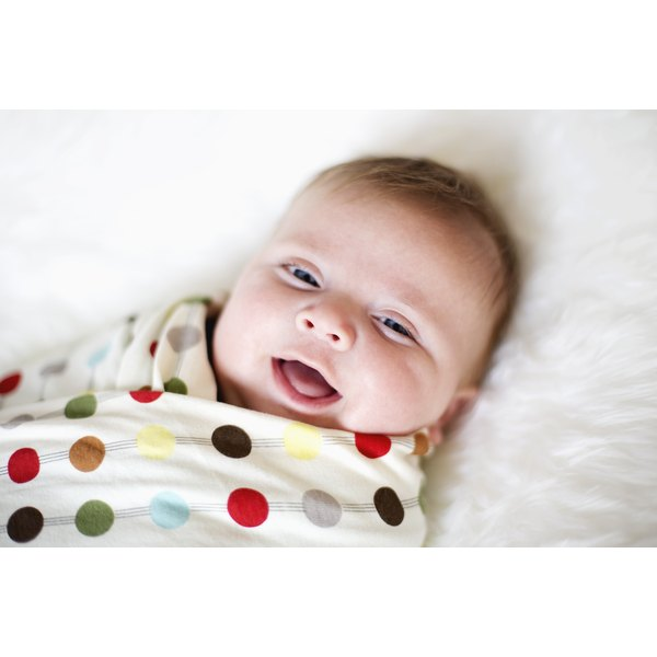 A smiling baby swaddled in a polka-dotted blanket.