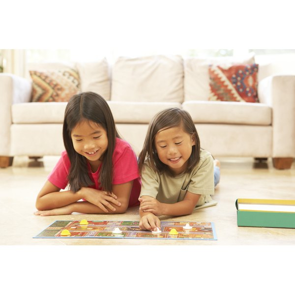 Two children playing with a board game.