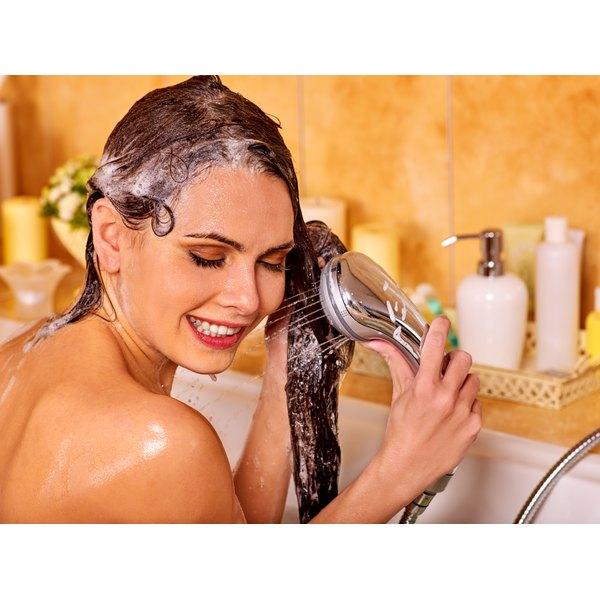 A woman shampoos her hair.