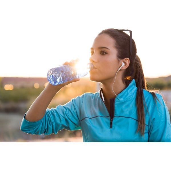A woman is drinking from a water bottle.
