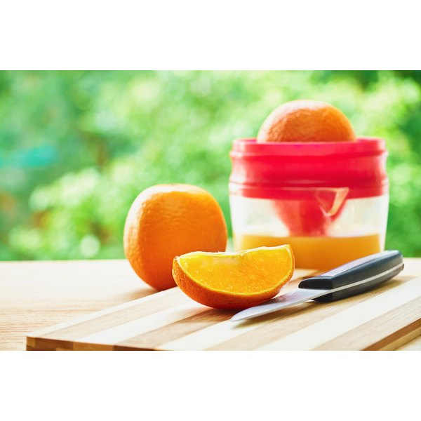A juice extractor with a knife and orange next to it.