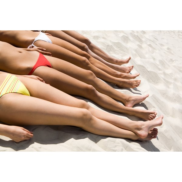 A close-up of a group of women in bikinis laying on the sand at the beach.