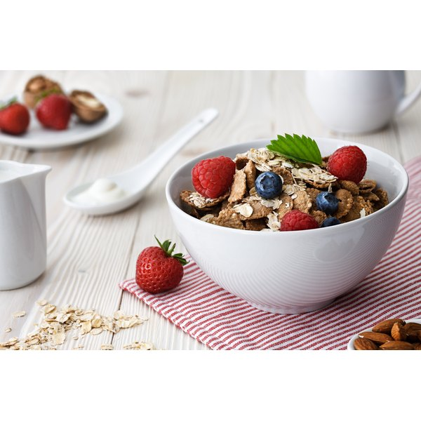 A bowl of multigrain cereal with raspberries.