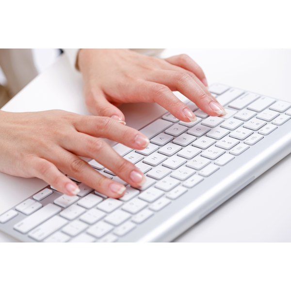 A woman types on a keyboard at her desk.