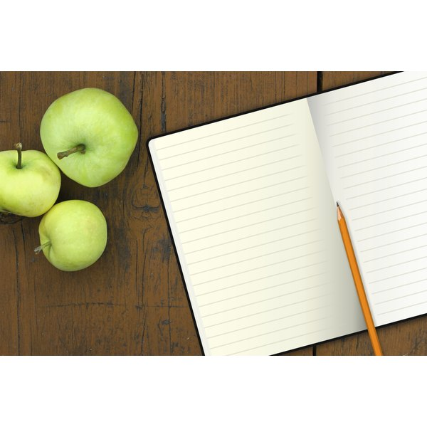 An open journal on a table next to a bunch of apples.