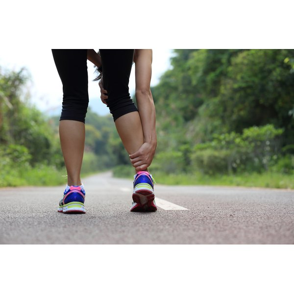 A woman has leg cramps while on a run.