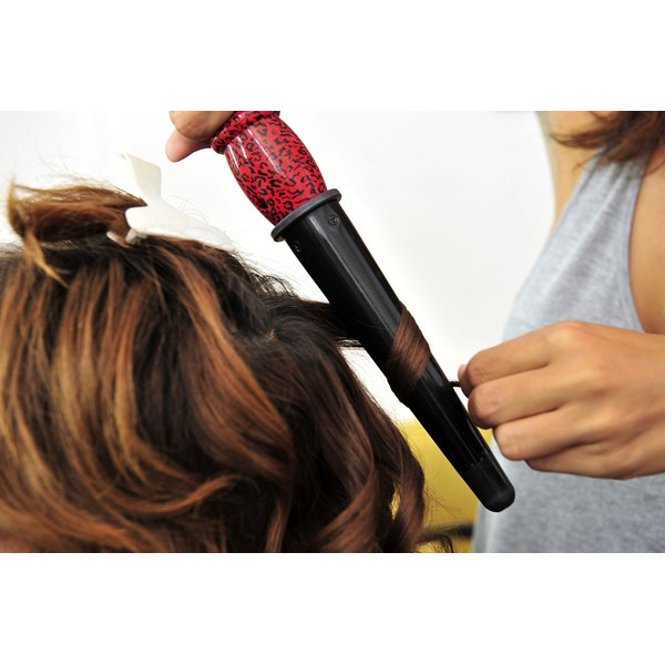 A woman getting her hair curled with a clampless curling iron.