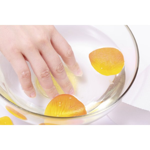 A woman soaking her fingernails in a bowl with clear liquid and orange flower petals.