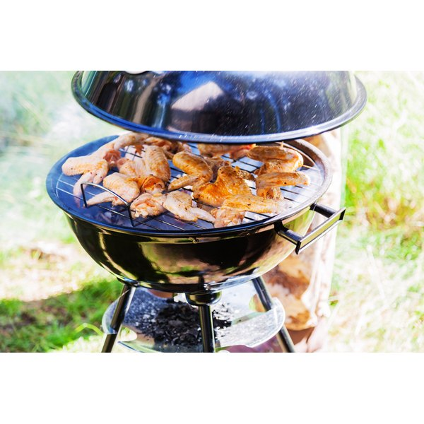 A man uncovering chicken wings on a charcoal grill in the yard.