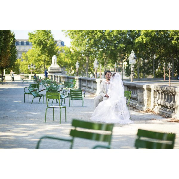 A bride and groom sitting at a cafe table in Tuileries gardens in Paris, France.