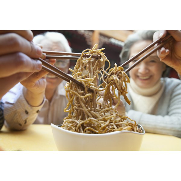 People sharing noodles with brown sauce.