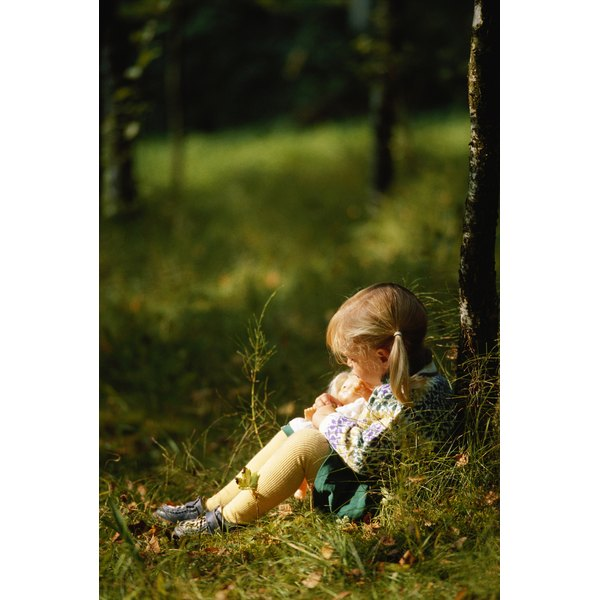 Child sitting against tree.