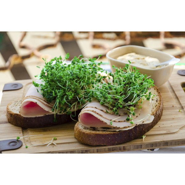 Meat and sprouts on sprouted grain bread slices.